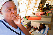 19 NOVEMBER 2010 - PORT-AU-PRINCE, HAITI:  Fifi Amante waits in front of a tent for her son, Mackenson (2nd bunk from bottom, orange blanket), to recover from cholera at a Medicins Sans Frontieres (MSF - Doctors Without Borders) cholera treatment center near the airport in Port-au-Prince. Cite Soleil, a sprawling slum area in PAP is ground zero for the cholera epidemic in the Haitian capital. An outbreak of cholera in northern Haiti about a month ago has spread across the nation. Tens of thousands of people have been hospitalized and treated for cholera and more than 1,100 have died. Cholera is a water borne illness that causes severe diarrhea and death by dehydration in a matter of hours.       PHOTO BY JACK KURTZ    choleraepidemic