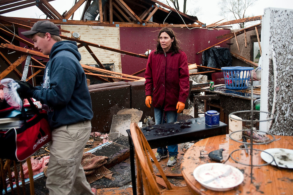 Cordova, Neb.-05/12/2014-Dacel Thomsen looks at the damage to her home as her daughter's boyfriend Nathan Oliva, 18, carries items out to a moving van May 12, 2014, the morning after a tornado hit in Cordova, NE. <br />