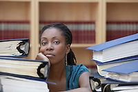 Office worker sitting behind stacks of documents in office portrait