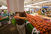 Jonathan Gold, a Pulitzer Prize winning food critic for the LA Weekly shopping at the Pasadena Farmers' Market on a Saturday morning. Because restaurant reviewers try to keep their identity secret in order to write unbiased reviews, Jonathan agreed to be photographed under the condition his face be obscured.  (Jonathan Gold is featured in the book What I Eat: Around the World in 80 Diets.) MODEL RELEASED.