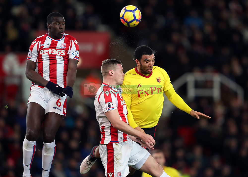 Watford's Troy Deeney battles with the ball in the air with Stoke City's Ryan Shawcross and Kurt Zouma (left) during the Premier League match at the bet365 Stadium, Stoke.