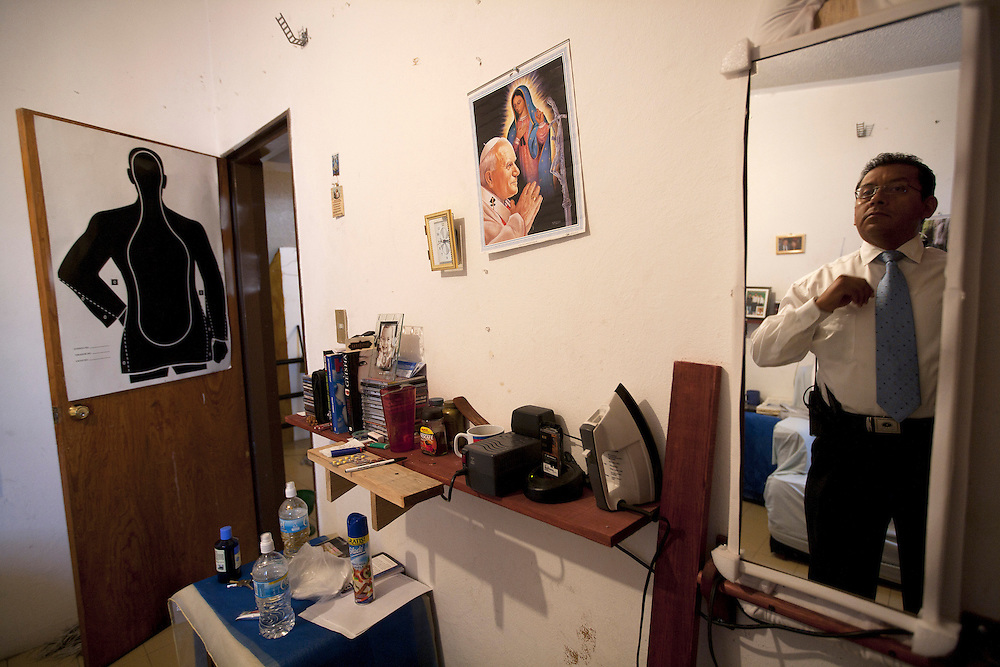 A Mexican bodyguard prepares for a long day of work, in what feels like a college dormitory setting. Several of his employer's bodyguards share this house while on duty. Room decor shifts between work related items used as wall art and religious ephemera.