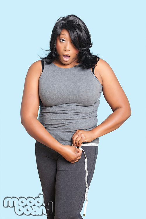 Portrait of overweight mixed race woman measuring waist over blue background