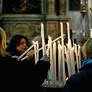 VENICE, ITALY - DECEMBER 13:  Pilgrims light candles inside the church of Saint Geremia where the relics of Santa Lucia (Saint Lucy) are housed on December 13, 2010 in Venice, Italy. Saint Lucy's Day (Santa Lucia) celebrated on December 13th, is observed in Scandinavian countries but also in Northern Italy, Malta and some Mediterranean countries.