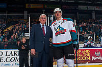 KELOWNA, CANADA - JANUARY 10: Cal Foote #25 of the Kelowna Rockets stands with President and General Manager, Bruce Hamilton to acknowledge his gold  medal win with Team Canada at the World Junior Championships on January 10, 2017 at Prospera Place in Kelowna, British Columbia, Canada.  (Photo by Marissa Baecker/Shoot the Breeze)  *** Local Caption ***