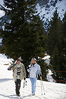 Skiing couple walking carrying skis on shoulders on ski slope