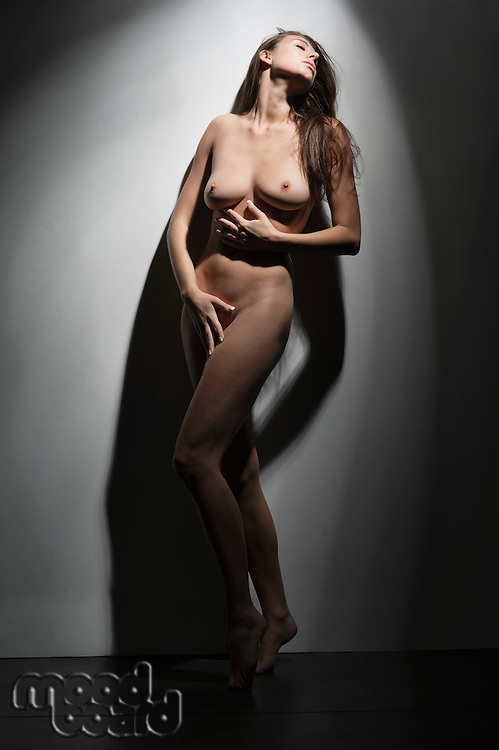 Sensual young woman standing naked against wall