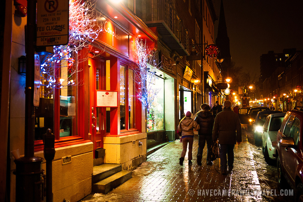Quebec City Old Town street at night in winter after a new snowfall making the cobblestone street glisten in the lights.