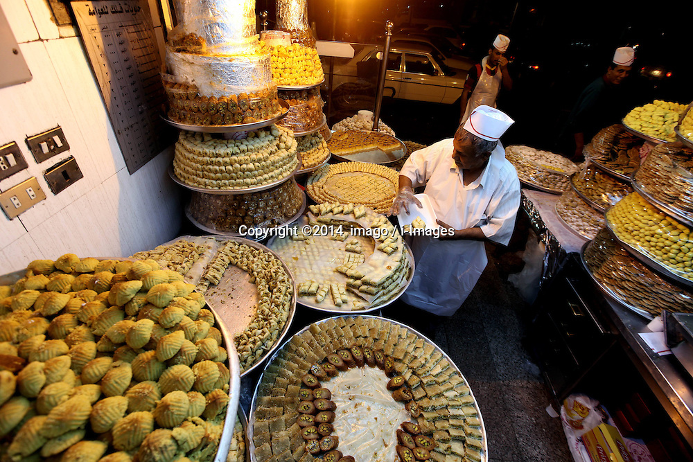 Image ©Licensed to i-Images Picture Agency. 28/07/2014. Amman, Jordan. <br /> 61981777<br /> A Jordanian man sells sweets for the upcoming Eid al-Fitr in downtown Amman, Jordan, on July 27, 2014. Eid al-Fitr, a major Muslim holiday, marks the end of the holy month of Ramadan. Picture by  imago / i-Images<br /> UK ONLY