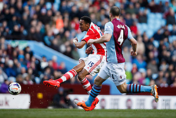 Stoke Midfielder Steven N'Zonzi (FRA) shoots as Aston Villa Defender Ron Vlaar (NED) tracks back - Photo mandatory by-line: Rogan Thomson/JMP - 07966 386802 - 23/03/2014 - SPORT - FOOTBALL - Villa Park, Birmingham - Aston Villa v Stoke City - Barclays Premier League.