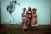 Three foreign tourists display their body tattooed in volcanic mud, an ancestral technique, as they poses for a photo aside a stylized graffiti depicting a bird, symbol of the Rapa Nui culture during a festival named Tapati Rapa Nui in Hanga Roa, Rapa Nui, Saturday, Feb. 12, 2011. As Chile  tries to push globalization into the island with the same power the Pacific waves reach its rocky shores, boundaries of race become blurrier in the most important Polynesian island, and during the Tapati festival, a former native week long celebration, only blue eyed or really white skinned people can be spotted like foreigners.