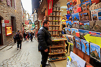 Souvenir shops, hotels and restaurants line the narrow cobblestone street through Mont San Michel, off the coast of Normandy, France.