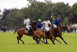 La Indiana (white shirts) compete against Park Place (blue shirts) in the Cartier Queen's Cup final at Guards Polo Club, Windsor Great Park, Surrey.