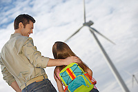 Father embracing daughter (5-6) at wind farm