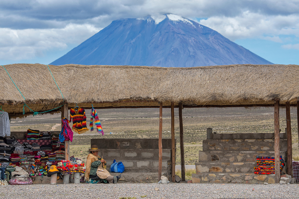South America,Peru, Altiplano, native woman knitting near volcano