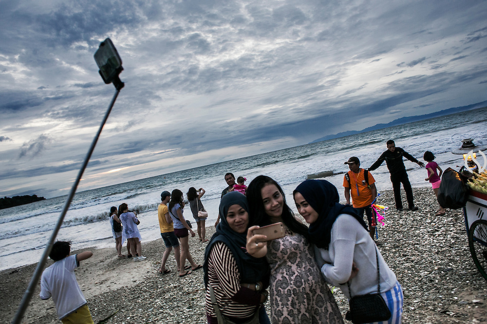 BALI, INDONESIA; APRIL 26, 2015: Tourists take group selfie pictures at Jimbaran beach on Sunday, April 26, 2015.