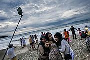 BALI, INDONESIA; APRIL 26, 2015: Tourists take group selfie pictures at Jimbaran beach on Sunday, April 26, 2015.