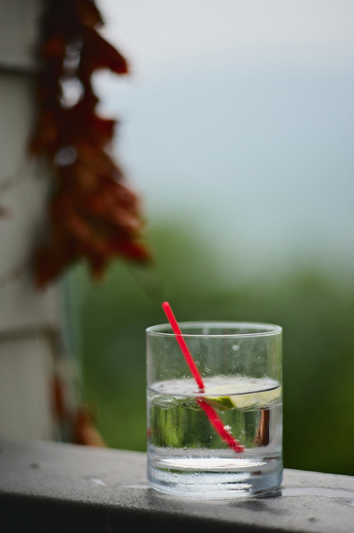 Drinking glass with red straw on porch railing