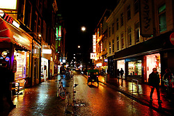 Downtown Amsterdam street at night.