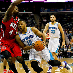 Jan 1, 2013; New Orleans, LA, USA; New Orleans Hornets shooting guard Eric Gordon (10) draws contact and a foul from Atlanta Hawks power forward Anthony Tolliver (4) during the first quarter of a game at the New Orleans Arena. Mandatory Credit: Derick E. Hingle-USA TODAY Sports
