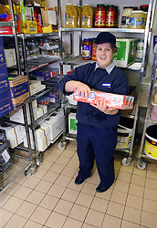 Woman with learning disability holding food carton in storage area of kitchen,