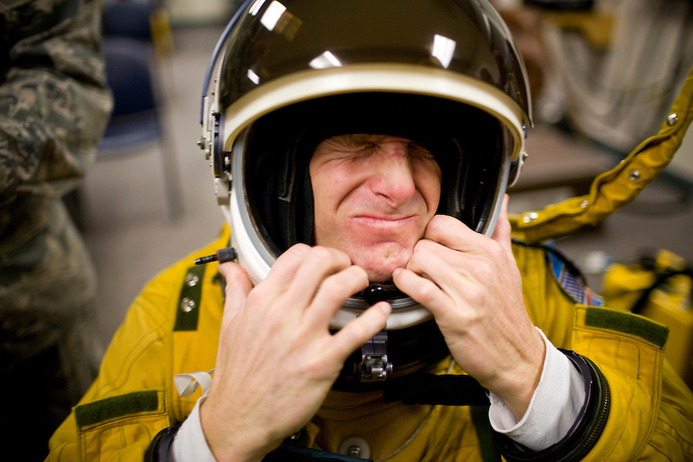 """U2 pilot Major Eric Shontz wriggles into his pressurized flight suit before a """"high-flight"""" at Beale Air Force Base February 24, 2010 in Linda, Calif."""