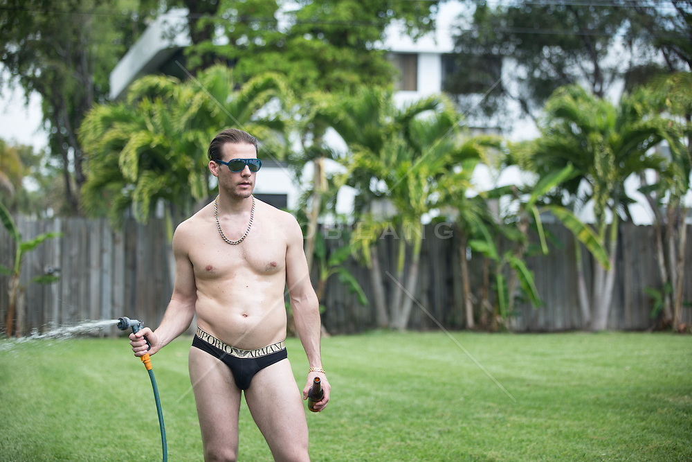 out of shape man in a bikini watering his lawn and holding a beer in Florida