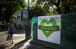 "© Licensed to London News Pictures. 23/08/2019. London, UK. A man walks past a Granfell sign with the words ""FUCK BORIS"" spray painted across it, as preparations begin ahead of the 2018 Notting Hill Carnival which starts this weekend. Warm weather is expected over the bank holiday weekend with carnival attracting over 1 million people to the capital. Photo credit: Ben Cawthra/LNP"
