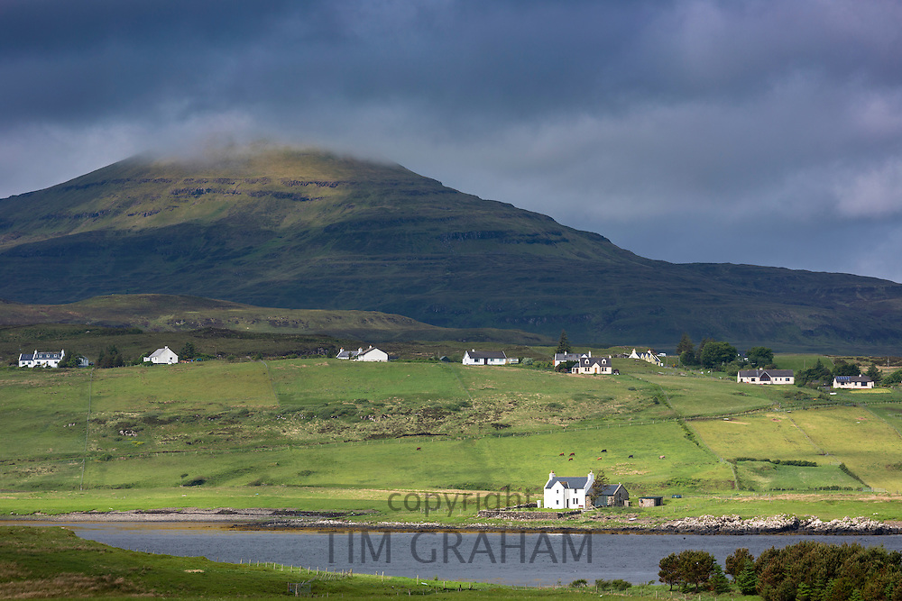 White croft cottages nestled in hamlet by mountain and Loch Vatten under grey clouds at Roag on the Isle of Skye, Western Isles of Scotland, UK