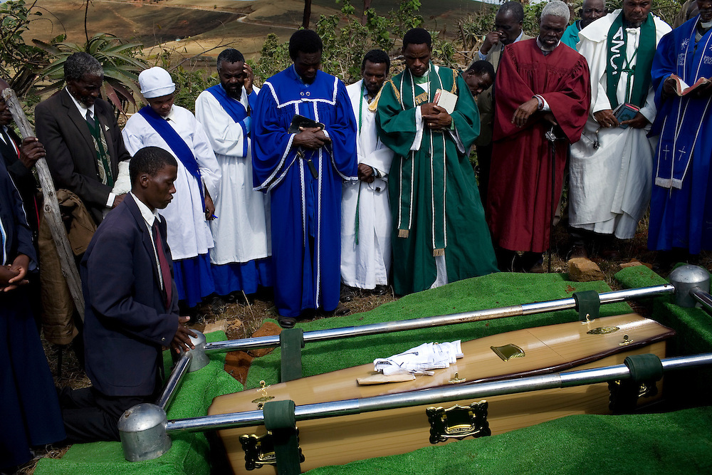 Family and friends bury the casket during the funeral of Sindiswa Sakubona, a woman who died with TB. Her husband, a former mine worker, also passed away from TB in 2001.  The couple leaves behind 7 oprhaned children. Sindiswa's father, also an ex miner, currently has TB and her brother used to have the disease.TB is common among ex-miners in Eastern Cape.  Once a miner has contracted TB the disease can lie in wait for more than 10 years until the patients immune system is weakened and the disease becomes active.  South African Gold miners are particularly vulnerable to contracting TB because of the small, poorly ventilated work conditions, high rates of TB and high rates of silicosis, a lung disease often found in miners that increases the chance of catching TB.