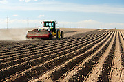 Farm machinery planting potatoes.