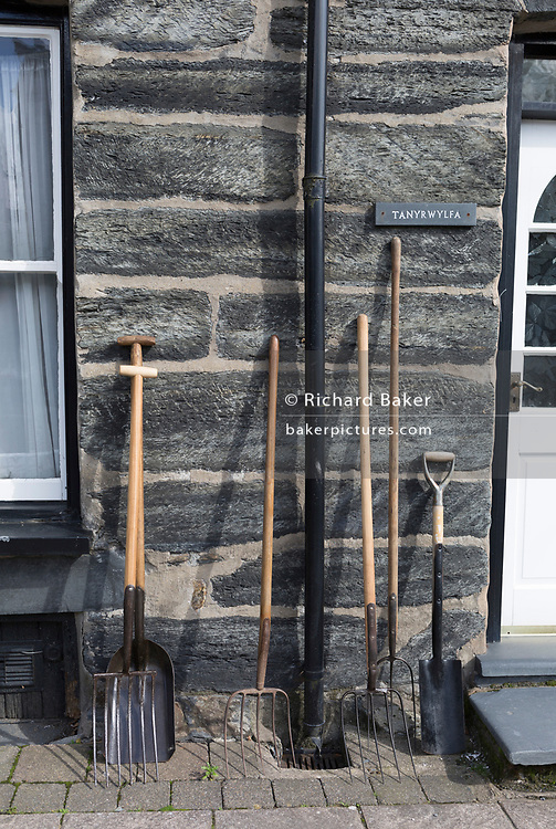 Garden implememts and farming tools lean against the wall of a house in Machynlleth during the weekly Wednesday market, on 12th September 2018, in Machynlleth, Powys, Wales.