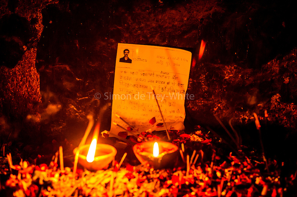 4th December 2014, New Delhi, India. Votive candles burn with photocopied requests left by believers to Djinns in the ruins of Feroz Shah Kotla in New Delhi, India on the 4th December 2014<br /> <br /> PHOTOGRAPH BY AND COPYRIGHT OF SIMON DE TREY-WHITE a photographer in delhi<br /> + 91 98103 99809. Email: simon@simondetreywhite.com<br /> <br /> People have been coming to Firoz Shah Kotla to leave written notes and offerings for Djinns in the hopes of getting wishes granted since the late 1970's, as many individual Djinns are thought to occupy the complex believers distribute photocopies throughout. <br /> Feroz Shah Tughlaq (r. 1351&ndash;88), the Sultan of Delhi, established the fortified city of Ferozabad in 1354, as the new capital of the Delhi Sultanate, and included in it the site of the present Feroz Shah Kotla. Kotla literally means fortress or citadel. The pillar, also called obelisk or Lat is an Ashoka Column, attributed to Mauryan ruler Ashoka. The 13.1 metres high column, made of polished sandstone and dating from the 3rd Century BC, was brought from Ambala in 14th century AD under orders of Feroz Shah. It was installed on a three-tiered arcaded pavilion near the congregational mosque, inside the Sultanate's fort. In centuries that followed, much of the structure and buildings near it were destroyed as subsequent rulers dismantled them and reused the spolia as building materials.