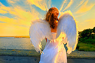 Angel girl seen from behind with spread wings and long brown hair blowing in wind. Teen or young adult angel at wood pier railing and facing marshland and water and golden dusk sky. Taken at Norman J. Levy Park and Preserve in Merrick, Long Island, New York, USA. Nikon D700 with Nikkor 14-24mm f/2.8 ultra wide angle lens.