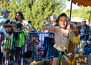 Old Bethpage, New York, U.S. 29th September 2013.  Young children ride an old-fashioned merry-go-round at The Long Island Fair. A yearly event since 1842, the county fair is now held at a reconstructed fairground at Old Bethpage Village Restoration.