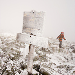 Man winter hiking.  Rime ice covers the rocks and a trail sign on Mount Washington in New Hampshire's White Mountains.  Nelson Crag Trail.  March. (MR)