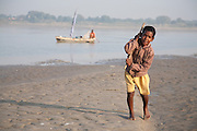A boy drags a sailing boat by a rope up stream on the river Ganges, Uttar Pradesh, India
