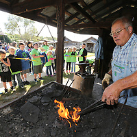 Boyd Yaraborough shows students the art of blacksmithing during Friday's annual Dogtrot Heritage Festival at the Oren Dunn Muesuem.