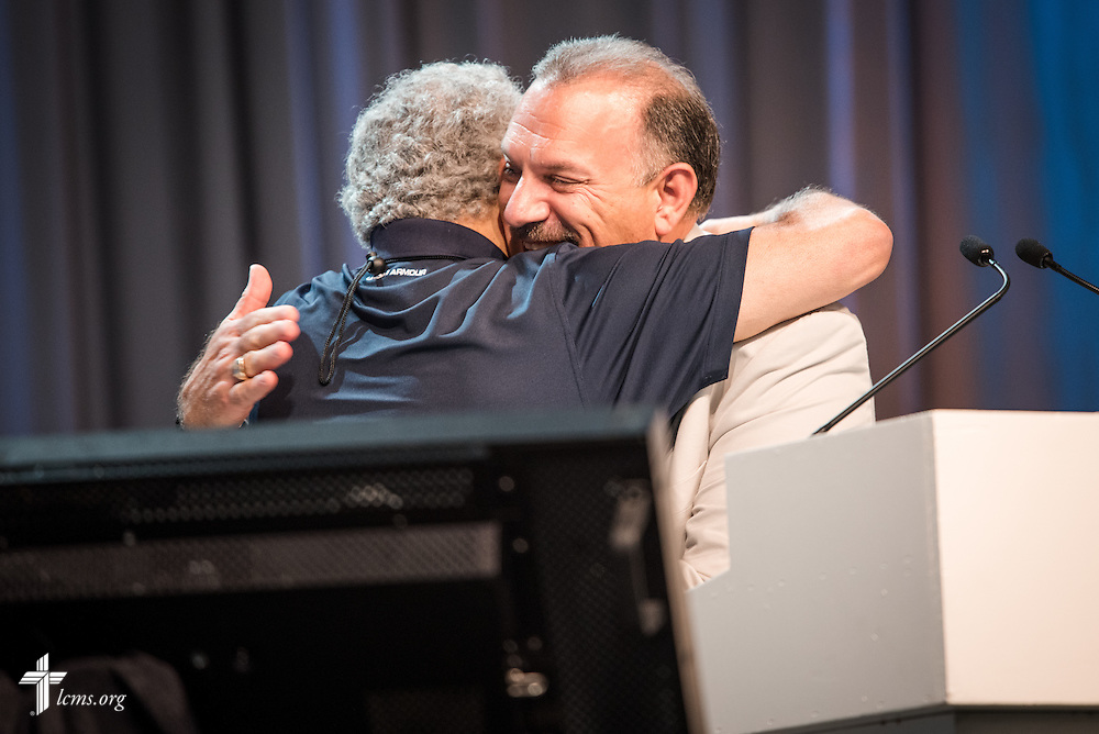 Rev. Nabil Nour, newly-elected LCMS third vice-president, hugs the Rev. Greg Walton, president of the LCMS Florida-Georgia District, for an embrace of forgiveness after mispronouncing Nour's last name the day before, on Monday, July 11, 2016, at the 66th Regular Convention of The Lutheran Church–Missouri Synod, in Milwaukee. LCMS/Frank Kohn