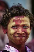 A boy whose face is stained with colored dye during the Holi festival, a Hindu spring festival, also called the Festival of Colors. On the second day, known as Dhulandi, people spend the day throwing colored powder and water at each other. New Delhi, India.