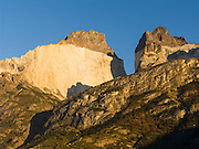 A golden sunrise brightens the peak of Cuerno Principal seen from Albergue Los Cuernos, a refuge (hut) in Torres del Paine National Park, Chile, Patagonia, South America.