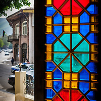 A colourful glass mosaic window frames a lack luster view outside making for an odd contrast.