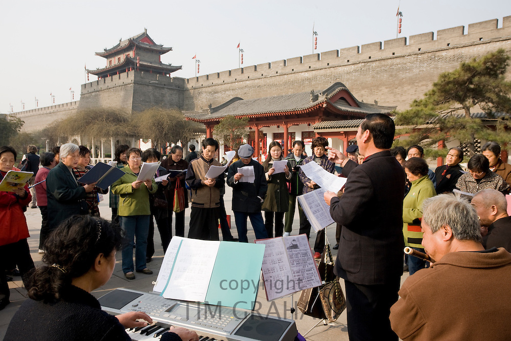 People gather to form an informal choir, part of the morning exercise in the park by the City Wall, Xian, China
