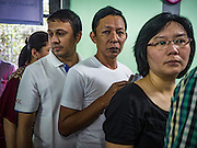 08 NOVEMBER 2015 - YANGON, MYANMAR: People stand in line to get their ballots at a polling place in central Yangon. The citizens of Myanmar went to the polls Sunday to vote in the most democratic elections since 1990. The National League for Democracy, (NLD) the party of Aung San Suu Kyi is widely expected to get the most votes in the election, but it is not certain if they will get enough votes to secure an outright victory. The polls opened at 6AM. In Yangon, some voters started lining up at 4AM and lines were reported to long in many polling stations in Myanmar's largest city.      PHOTO BY JACK KURTZ