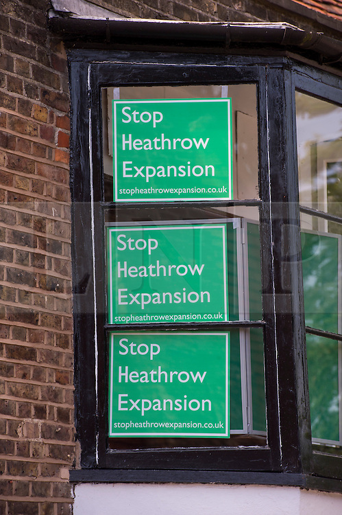 """© London News pictures...  01/07/2015. Harmondsworth, UK. """"Stop Heathrow Expansion"""" signs in the window of a building in Harmondsworth in West London. Harmondsworth is due to be demolished to make way for a third runway at Heathrow Airport if plans go ahead. The airports commission today (Weds) gave it's backing for the £18.6bn plan for a third runway at Heathrow. Photo credit: Ben Cawthra/LNP"""