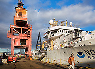 GMD shipyard is a dry dock at Brooklyn's Navy Yard.  A worker is passing one of the vessels there for repair.