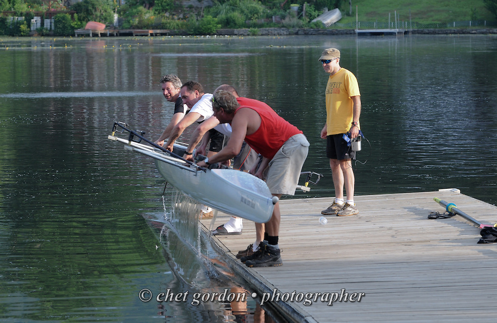 A four-man team of rowers remove their boat from the water after a morning row in Greenwood Lake, NY on Tuesday, July 9, 2013.  © Chet Gordon/THE IMAGE WORKS