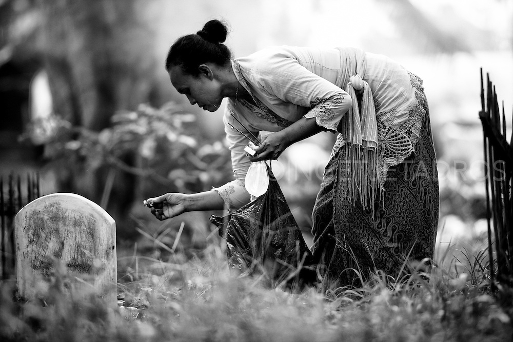Woman tidying up around a grave at a burial site.<br />