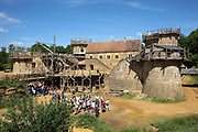 Group of visitors at the Chateau de Guedelon, a castle built since 1997 using only medieval materials and processes, photographed in 2017, in Treigny, Yonne, Burgundy, France, with lifting gear or squirrel cage with double drum, and (left-right) the Corner Tower, Chapel Tower, North Range or Logis Seigneurial and Great Tower or Tour Maitresse. The Guedelon project was begun in 1997 by Michel Guyot, owner of the nearby Chateau de Saint-Fargeau, with architect Jacques Moulin. It is an educational and scientific project with the aim of understanding medieval building techniques and the chateau should be completed in the 2020s. Picture by Manuel Cohen
