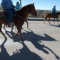 A group of horseback riders cross the 491 bridge in Shiprock Saturday as part of the Northen Navajo Nation fair parade.